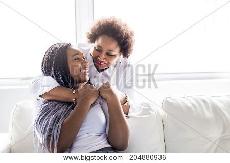 A affectionate mother and daughter sitting on sofa