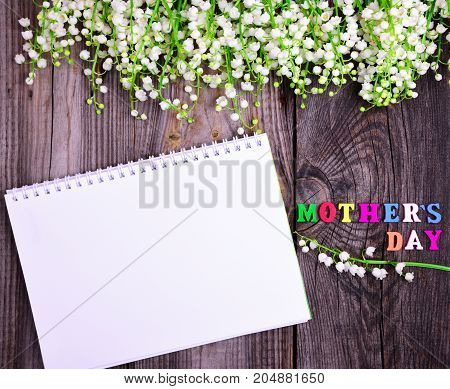 empty open white notebook and a congratulatory inscription with a mother's day on a gray wooden background at the top a bouquet of blossoming lilies of the valley