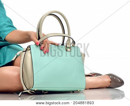 Beautiful female legs wearing summer shoes in blue designers dress and blue mint woman clutch bag isolated on white background