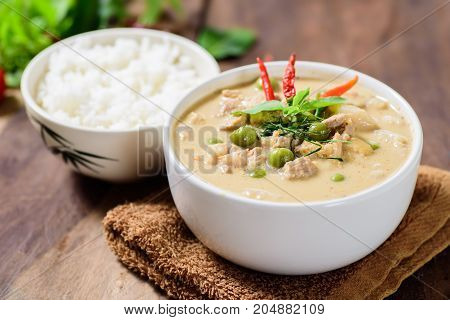 Thai food (Phanaeng curry),red curry with pork and cooked rice in a bowl on wooden background