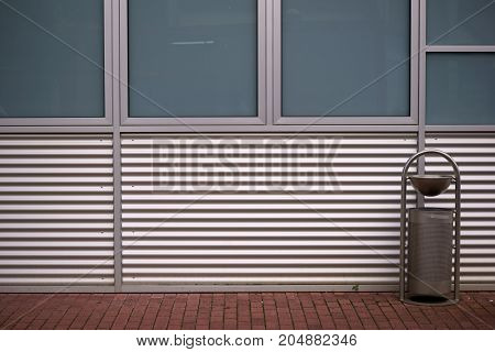 The sheet metal panel of a modern building in front with a trash can.