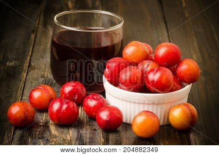 Plum fruit (Julee) and juice on wooden background