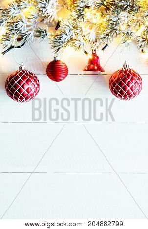 Vertical White Wooden Background With Copy Space For Advertisement. Christmas Banner With Red Christmas Decoration Like Balls And Bells. Fir Branches With Fairy Lights.