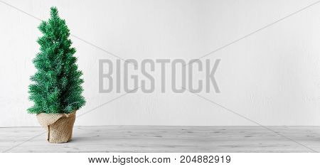 Green Christmas Tree With Brown Wooden Background And Gray Cement Wall. Christmas Greeting Card With Copy Space.