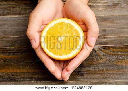 Sliced Navel orange fruit holding by hand on wooden background