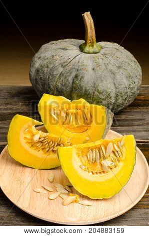 Slices of raw pumpkin on wooden plate for cooking