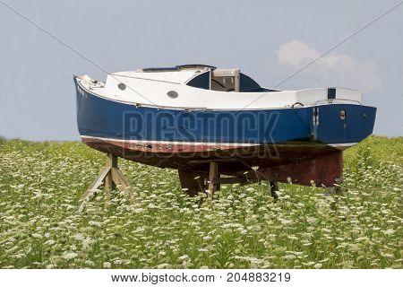 An old boat sitting in an open field.