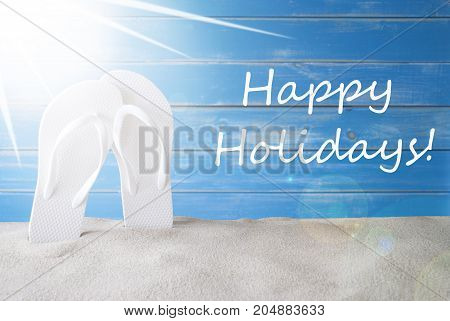 English Text Happy Holidays. Sunny Summer Greeting Card With Sand And Flip Flops. Blue Vintage And Shabby Chic Wooden Background.