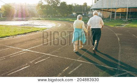 Senior couple taking a walk along the running track in summer. Healthy retirees enjoying morning walking on the stadium with camera lens flare.