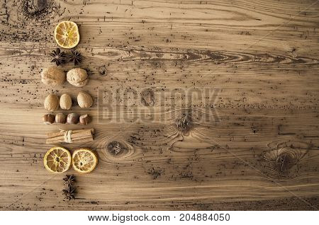 Nuts And Fruits Forming Shape Of Christmas Tree. Nuts Like Hazelnut, Walnut And Fruits Like Orange And Clove. Rustic Brown Wooden Background With Copy Space