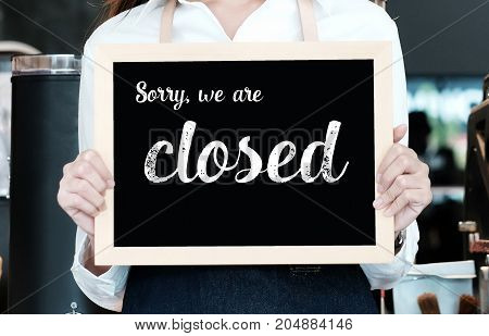 Hand holding closed sign chalkboard in font of cafe counter background food and drinks