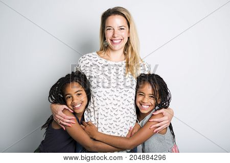 Two Afro twin child posing on a gray background studio with mother