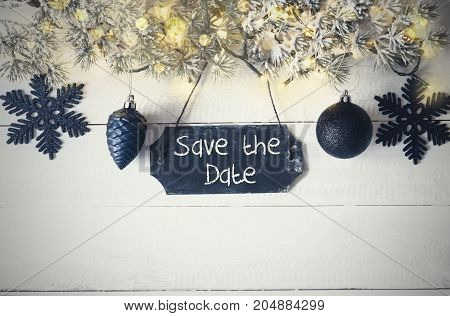 Black Chirstmas Plate With English Text Save The Date. Fir Branch With Fairy Lights On Wooden Background. Black Christmas Decoration Like Balls And Snowflakes.