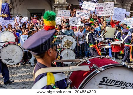 Antigua Guatemala - September 15 2017: School band marches past protesters protesting against government corruption in front of city hall on Guatemala's Independence Day.