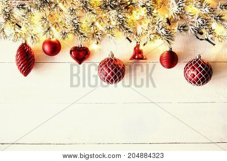 White Wooden Background With Copy Space. Christmas Banner With Red Christmas Decoration Like Balls, Hearts And Bells. Fir Branches With Fairy Lights.