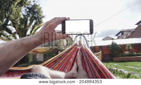 A View from behind a young woman lying in a hammock and looking at smartphone