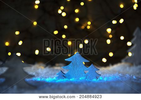 Wooden Christmas Tree In Blue Spotlight On White Snow. Bright Sparkling Lights In Background.