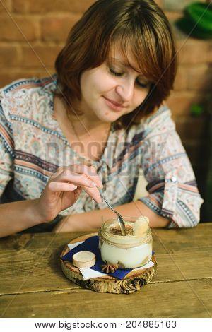 white caucasian girl hipster eating tiramisu in cafe