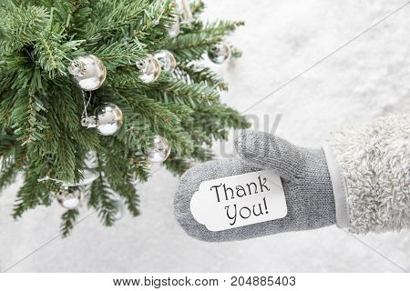 Glove With Label With English Text Thank You. Green Christmas Tree With Silver Balls On Snow In Background. Seasonal Greeting Card.