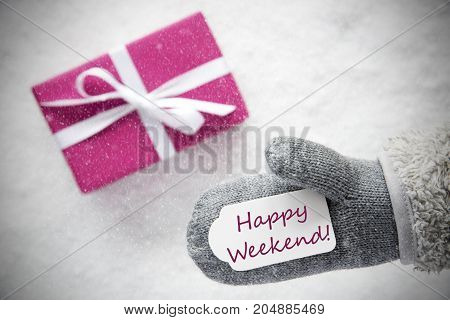 Glove With Label With English Text Happy Weekend. Pink Or Rose Gift Or Present On Snow In Background. Seasonal Greeting Card With Snowflakes