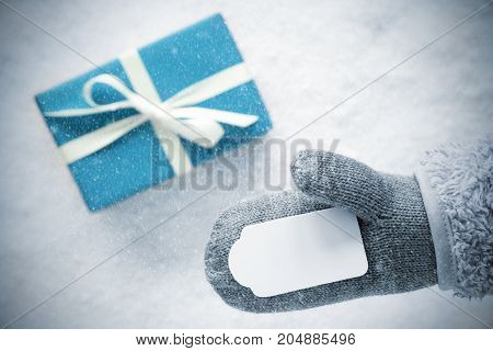 Glove With Label Copy Space For Advertisement. Turquoise Gift Or Present On Snow In Background. Seasonal Greeting Card With Snowflakes.