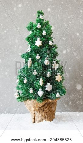 Vertical Green Fir Tree With Silver And Gold Christmas Ball Ornament. Gray Cement Background And Snow. Christmas Greeting Card With Snowflakes.