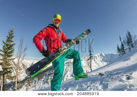 Portrait Young Man Ski Goggles Holding Ski In The Mountains