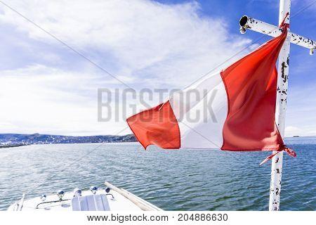 Sailing under the Peruvian flag on Lake Titicaca, Puno Region