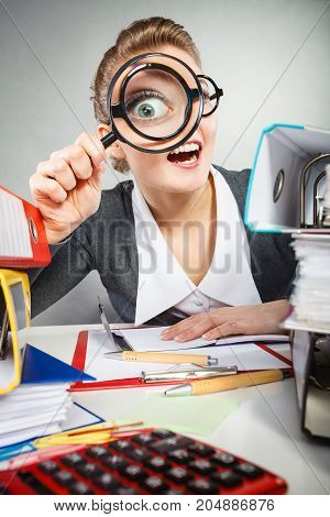 Craziness and satisfaction from work. Crazy bizarre funny secretary accountant businesswoman with big loupe. Woman surrounded by business equipment.