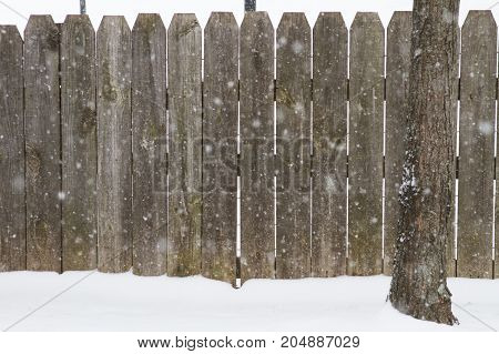 Blank wooden fence while its snowing out.