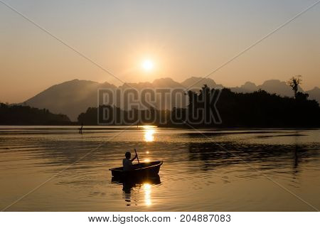 Beautiful sunrise and the shadow of a man who paddle a wooden boat in Srinagarindra Dam in Kanchanaburi, Thailand.