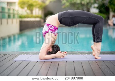 Beautiful young Asian woman doing yoga exercise near swimming pool. Healthy lifestyle and good wellness concepts