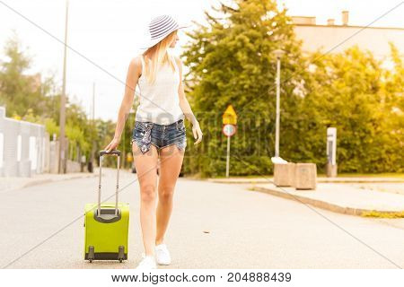 Travel adventure teenage journey concept. Attracitve woman wearing denim shorts white top and sneakers walking with green suitcase through city
