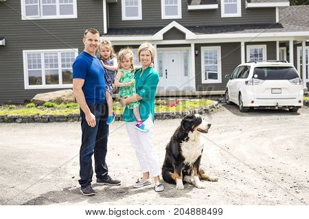 A happy family standing in front of the house
