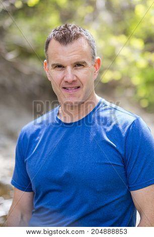 A Portrait Of Man Standing Outside In summer Landscape