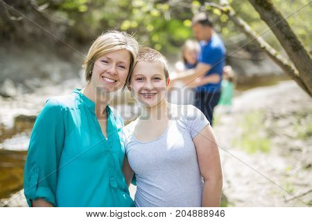 A Young smiling woman with her teen daughter outdoors