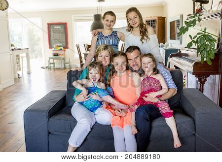 A happy family sitting on couch at home