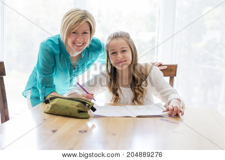 A Mother helping teenaged girl with homework