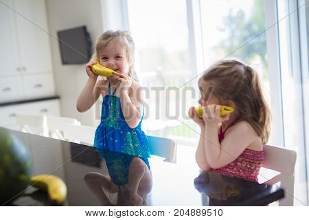 Two girls with bananas on the kitchen have fun phone