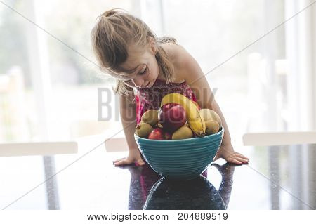 A Happy girl with a bowl of fruits at home