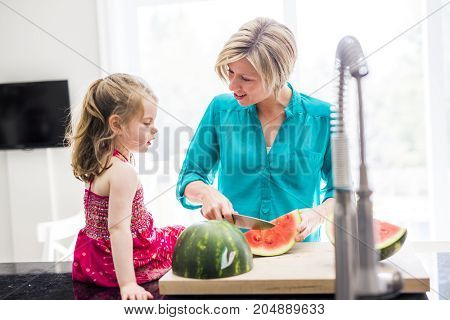 A Mother and daughter cooking dinner in kitchen
