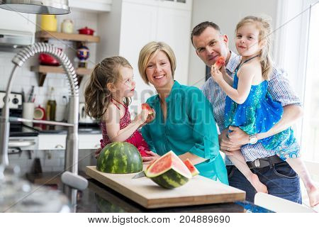 A family in the kitchen cuting the watermelon