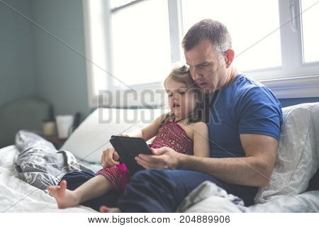 A father and daughter relax in bed with tablet computer