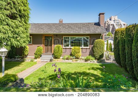 Front yard of residential house decorated with flowers on sunny day in British Columbia