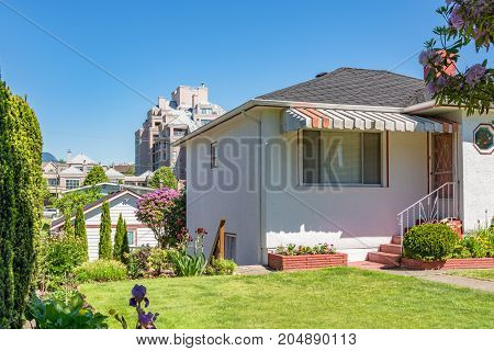 Front yard and entrance of residential house on sunny day in British Columbia