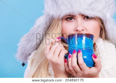 Blonde Woman In Winter Furry Hat Drinking