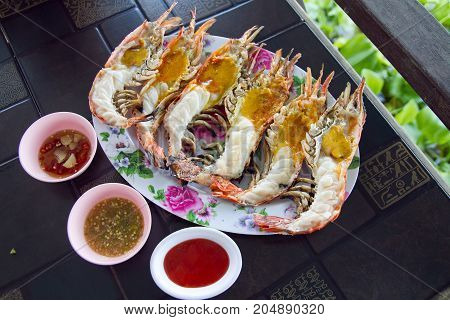 Grilled river prawns with spicy sauce on wooden table