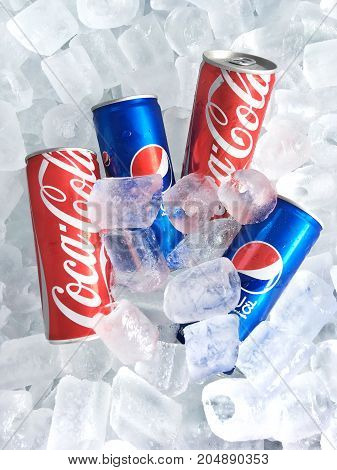 BANGKOK THAILAND - AUGUST 31 2017: Coca-Cola and Pepsi slim cans on ice background.