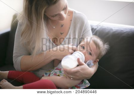 A Happy young mother with baby girl on sofa at home