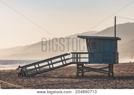 A lifeguard station with a foggy background and mountains on Zuma Beach in Malibu, California.